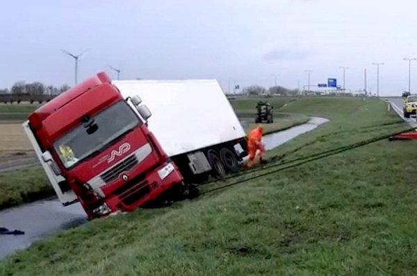 真粗暴!卡车掉进水沟竟靠生拉硬拽脱困